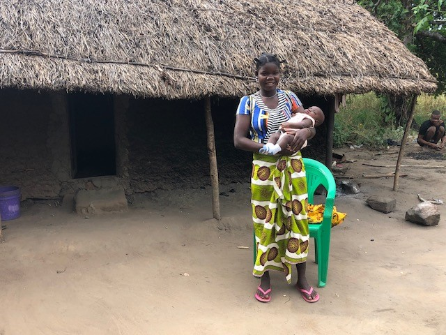 Diolista holds her healthy baby boy after a safe pregnancy, thanks in part to the three recommended doses of SP received from her TIPTOP community health worker (Credit: André Lamina / Jhpiego).